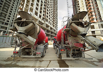 Two concrete mixer stand near unfinished tall high-rise...