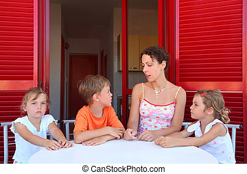 Mother and three children sit on verandah near an entrance...