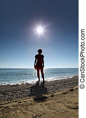 Silhouette of woman which stands on  beach in water opposite  sun