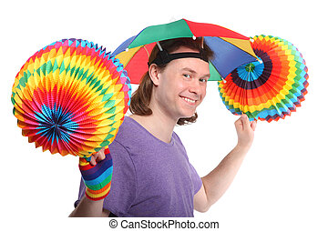 Portrait of happy man with rainbow hat umbrella on head and colorfull paper garland in hands