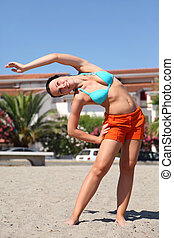 young beauty woman making gym exercises on beach and...