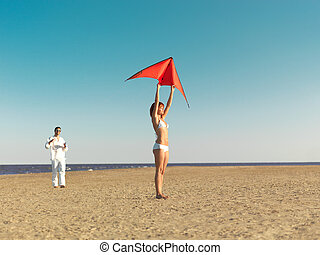couple launching red kite on sea shore - happy, young couple...