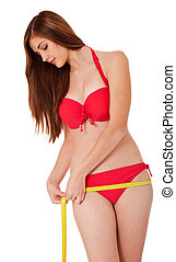 Diet - Attractive woman in bikini using measuring tape...