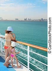 woman and her daughter standing on deck of cruise ship and looking at water.