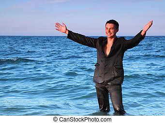 Smiling man in suit stands in sea and open hands at evening
