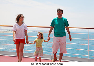 young family go for a walk on deck of ship and they are held...