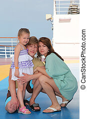 happy family with daughter on cruise liner deck, mother and father sitting on floor
