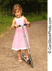 beautiful little girl in pink dress rides scooter on nature. forest could be seen in background