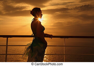 beautiful woman standing on deck of cruise ship and looking away. sunset.