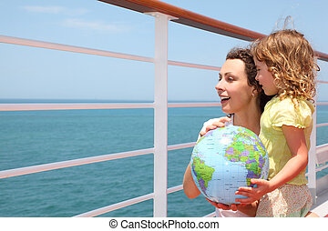 mother and daughter holding inflatable globe on cruise liner...
