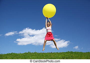 Woman by canicular day descend on inflatable ball on grass