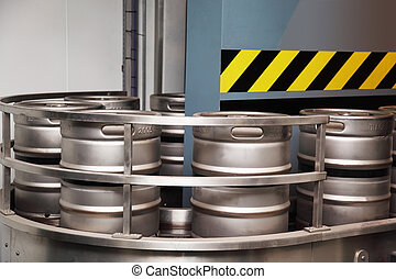 several aluminum beer barrels move on the conveyor blue wall...