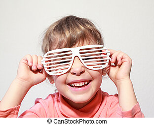 Portrait of little smiling girl, she try on white glasses-shutters