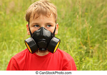 little boy in red shirt with black respirator on face is in...
