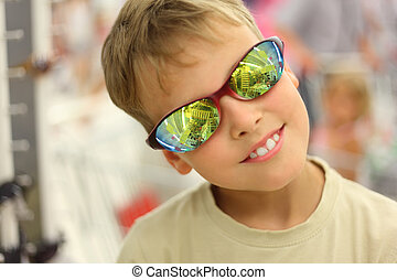 portrait of little boy trying sunglasses with reflection and...