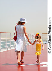 young mother and daughter walking on cruise liner deck, sunny day, view from back