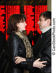 Man and woman in leather jacket standing in profile and embracing look to each other in eye on background of flight timetable