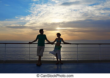 man and woman standing on deck of cruise ship. woman looking...