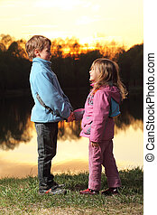 Little girl in pink clothes and boy in blue jacket holding hands and looking to each other on background of sunset