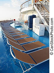 row of chaise longues on deck of cruise ship. golden morning...