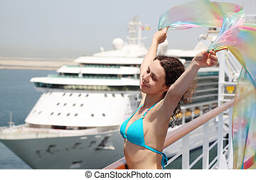 young beauty woman standing on cruise liner deck in bikini and holding pareo, half body