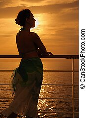 beautiful woman standing on deck of cruise ship and looking away. evening.