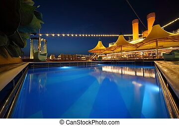 illuminated deck of ship at evening. swimming pool in center...
