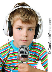 Little boy in striped shirt and headphone with microphone in hands