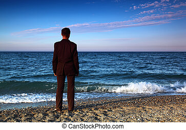 Barefooted man in suit stands back on stone coast at evening