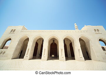 building with arcs and big doors of building inside Grand Mosque in Oman. Wide Angle.