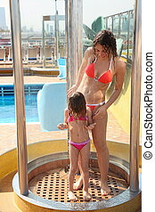 beautiful woman with her daughter both wearing swimming suit are taking shower on deck of cruise ship. woman looking at girl.