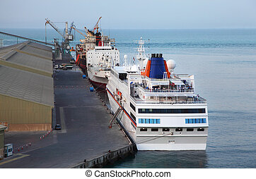 Big cruise liner, two cargo ships and crane at a port in Abu...