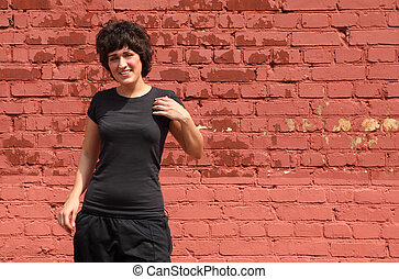 Portrait of girl in black clothes, she makes gymnastics on background of brick wall