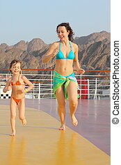 joyful woman with her daughter are running on deck of cruise...