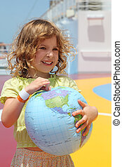 little girl standing on cruise liner deck and holding inflatable globe, half body