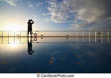 man with compact photo camera shooting morning sky from deck...