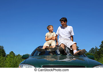 Father with  son sit on  roof of car in  day-time and speak
