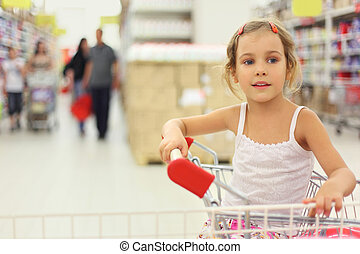 little girl sitting in store cart and looking at side,...