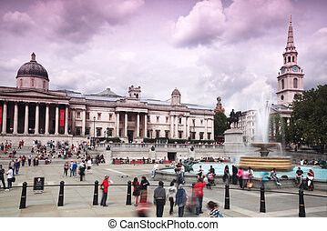 People stand at fountain at Trafalgar Square in front of the...