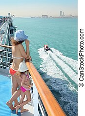 woman and her daughter standing on deck of cruise ship and looking at motor boat.