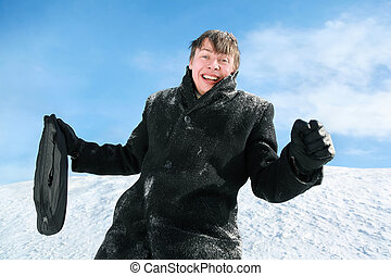 Man with brief-case stands by winter day on snow and rejoices