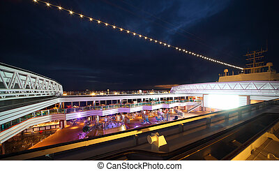 People enjoy night party on the deck of illuminated cruise...