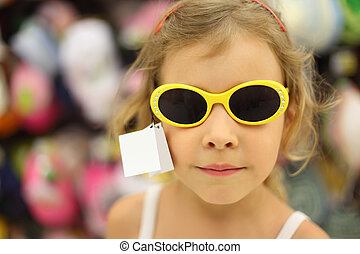 portrait of little girl trying sunglasses with yellow rim in...