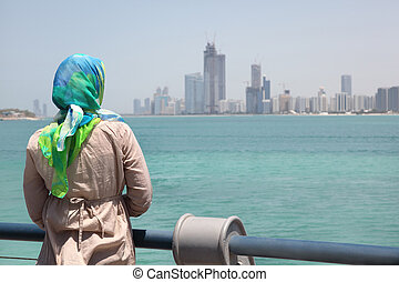 Girl in blue kerchief standing on the ship and watches Abu Dhabi buildings and seafront.