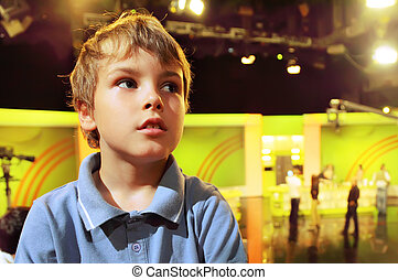 Little boy stands with folded hands in auditorium against...