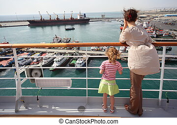 woman and her daughter standing and looking at ships in...