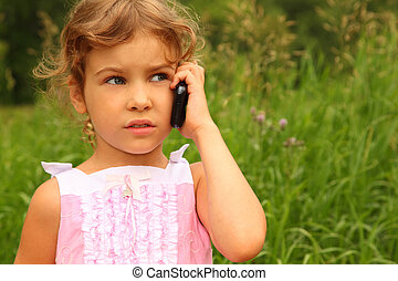 beautiful little girl in pink dress talking on cell phone outdoors