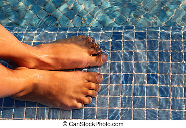 Small boy feet are jointed and putted in water of blue...