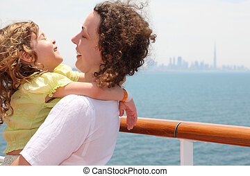 young mother carrying her daughter and laughing, standing on cruise liner deck, city on horizon