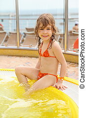 little girl wearing swimming suit sitting on edge of...